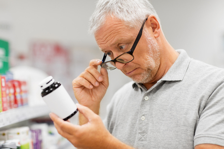 Photo pour senior male customer with drug at pharmacy - image libre de droit