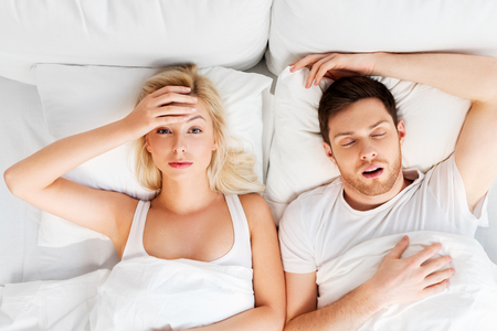 Photo pour unhappy woman in bed with snoring sleeping man - image libre de droit