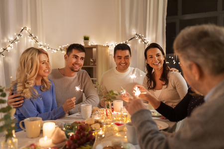 Foto de celebration, holidays and christmas concept - happy family with sparklers having fun at dinner party at home - Imagen libre de derechos
