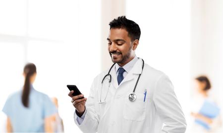 Foto für smiling indian male doctor with smartphone - Lizenzfreies Bild