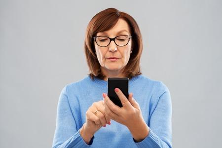 Foto per senior woman in glasses using smartphone - Immagine Royalty Free