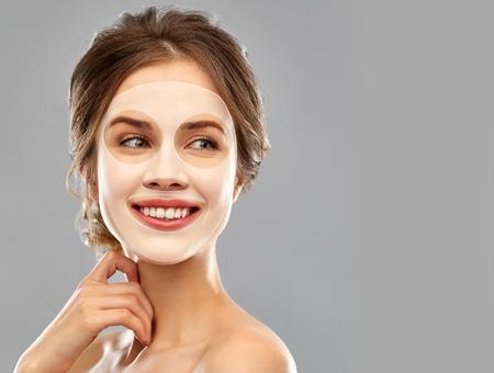 Photo pour smiling young woman wearing sheet facial mask - image libre de droit