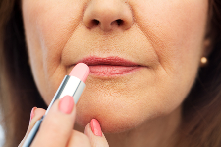 Photo pour close up of senior woman applying lipstick - image libre de droit