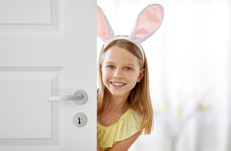 Photo for happy girl with easter bunny ears peeking out door - Royalty Free Image