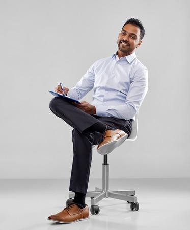 Foto de smiling indian businessman writing to clipboard - Imagen libre de derechos