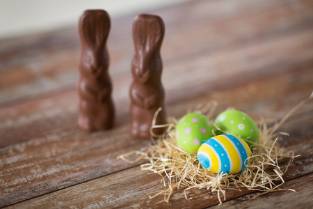 Photo for easter eggs in straw nest and chocolate bunnies - Royalty Free Image