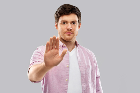 serious young man showing stop gesture