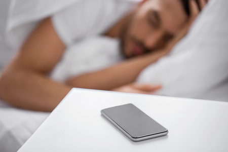 Photo pour technology and people concept - close up of smartphone on bedside table near young man sleeping in bed at home in morning - image libre de droit