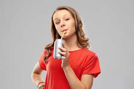 Photo pour girl drinking soda from can through paper straw - image libre de droit