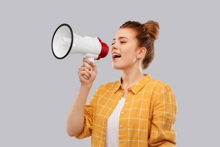 Photo pour communication, feminism and rights concept - red haired teenage girl in checkered shirt speaking to megaphone over grey background - image libre de droit