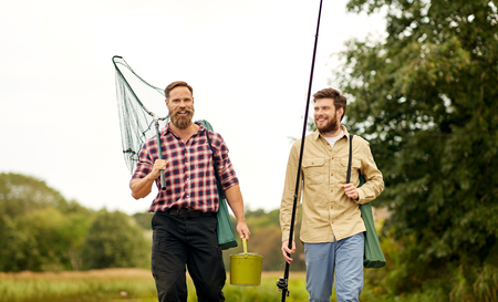 Photo pour friends with fishing rods and net walking outdoors - image libre de droit