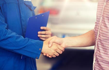 Photo pour auto mechanic and man shaking hands at car shop - image libre de droit