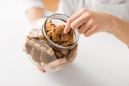 Photo pour close up of woman taking oatmeal cookies from jar - image libre de droit