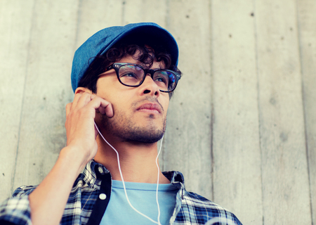 Foto per people, music, leisure and lifestyle - man with earphones listening to music on street - Immagine Royalty Free