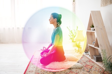 Photo for mindfulness, spirituality and healthy lifestyle concept - woman meditating in lotus pose at yoga studio over rainbow aura - Royalty Free Image