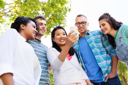 Photo pour Happy friends with smartphone at summer park - image libre de droit