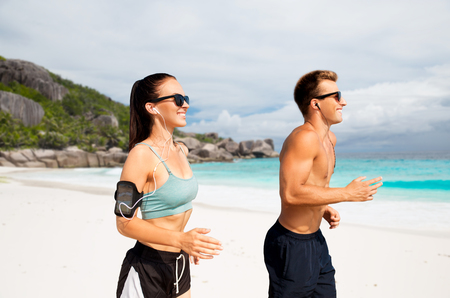 Foto de couple with phones and arm bands running on beach - Imagen libre de derechos