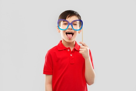 Photo pour happy boy with big paper glasses showing tongue - image libre de droit