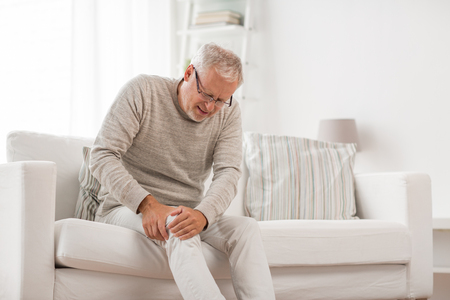 Foto de People, health care and problem concept - unhappy senior man suffering from knee ache at home - Imagen libre de derechos