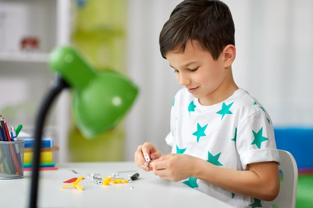 Photo for Childhood, hobby and leisure concept - little boy playing with building kit at home - Royalty Free Image