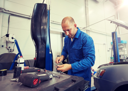 Photo pour car service, repair, maintenance and people concept - auto mechanic man with wrench and lamp working at workshop - image libre de droit
