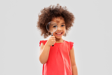 Photo for investigation, discovery and vision concept - happy little african american girl looking through magnifying glass over grey background - Royalty Free Image