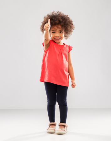 Photo pour Little African American girl showing thumbs up - image libre de droit