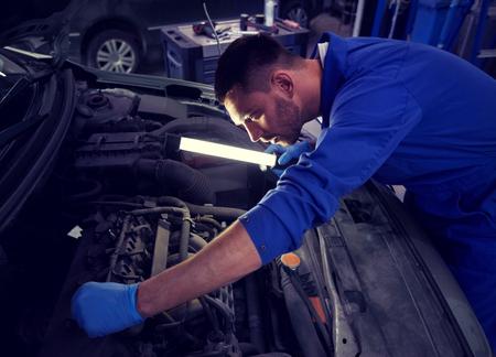 Photo pour Mechanic man with lamp repairing car at workshop - image libre de droit