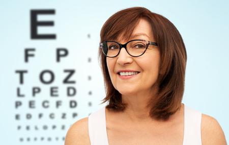 Photo pour Happy senior woman in glasses over eye test chart - image libre de droit