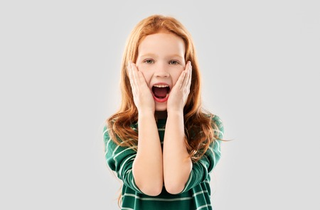 Photo pour shocked or surprised red haired girl screaming - image libre de droit