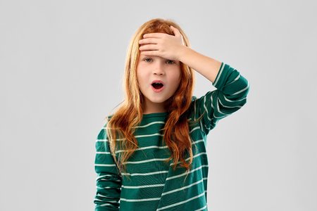 Photo pour shocked red haired girl holding to her head - image libre de droit