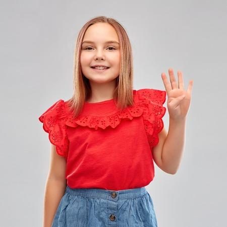 Photo pour smiling girl in red shirt showing four fingers - image libre de droit