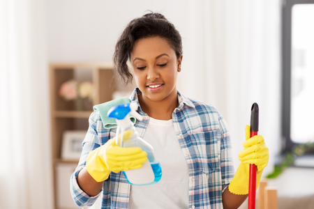 african american woman with detergent at home