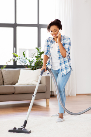 Photo pour african american woman with vacuum cleaner at home - image libre de droit