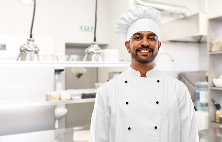 Photo pour Happy male Indian chef at restaurant kitchen - image libre de droit