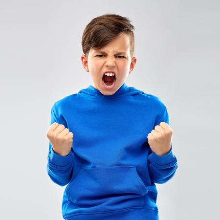 Photo pour An angry boy in blue hoodie celebrating success - image libre de droit