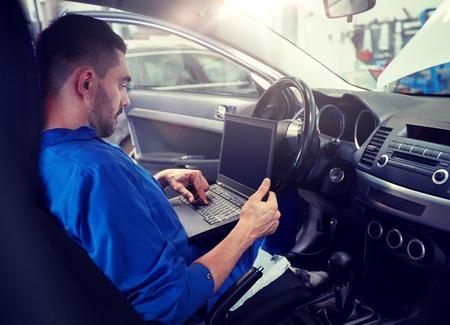 Photo pour mechanic man with laptop making car diagnostic - image libre de droit