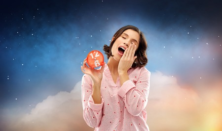 Photo pour sleepy woman in pajama with alarm clock yawning - image libre de droit