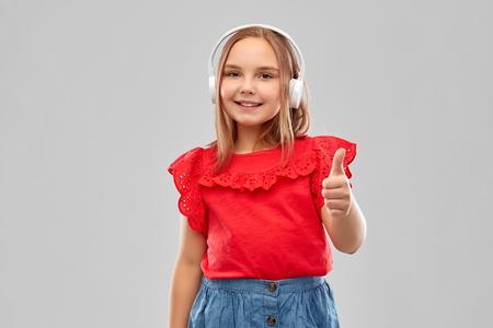 Foto de smiling girl in headphones listening to music - Imagen libre de derechos
