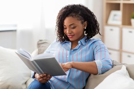 Foto de happy african american woman reading book at home - Imagen libre de derechos
