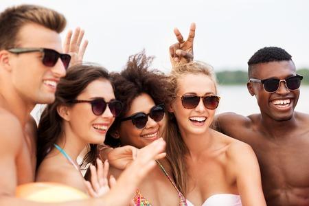 Photo pour happy friends in sunglasses on summer beach - image libre de droit