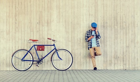 Foto per people, style, technology, leisure and lifestyle - young hipster man in earphones with smartphone and fixed gear bike listening to music at city street wall - Immagine Royalty Free
