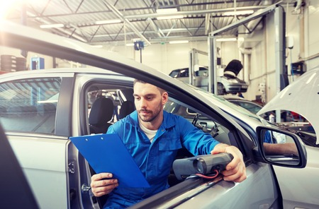 Photo pour service, repair, maintenance and people concept - mechanic man with automotive diagnostic scanner and clipboard checking car system at workshop - image libre de droit