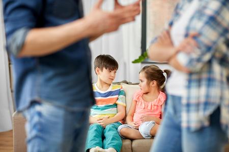 Photo pour Family problem, conflict and people concept - sad children watching their parents quarreling at home - image libre de droit