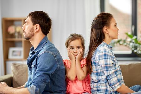 Foto de Family problem, divorce and people concept - unhappy father, mother and sad little daughter at home - Imagen libre de derechos