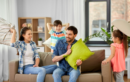 Photo for Family, childhood and people concept - happy father, mother, little son and daughter fighting by pillows and having fun at home - Royalty Free Image
