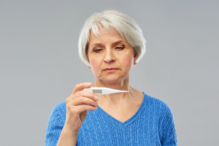 Photo for Health and fever concept - sick senior woman with thermometer over grey background - Royalty Free Image