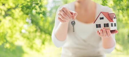 Photo pour close up of hands holding house model and keys - image libre de droit