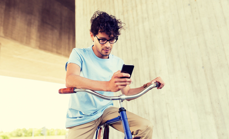 Photo for man with smartphone and fixed gear bike on street - Royalty Free Image