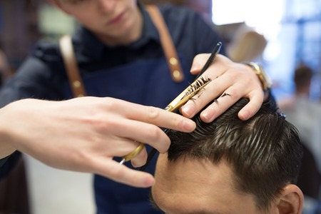 Foto für grooming, hairdressing and people concept - close up of male client and hairdresser with comb and scissors cutting hair at barbershop - Lizenzfreies Bild